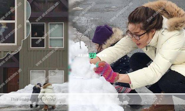 Linda Chung and her daughter, Kelly build a snowman outside their house