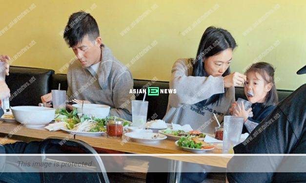 Edison Chen plays with his mobile phone while having dinner with Qin Shupei