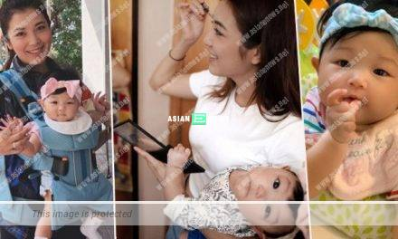 Strong Phoebe Sin applies make-up while carrying her daughter